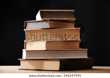 Stack of books on dark background - stock photo