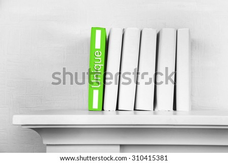Stack of books on shelf on wall background - stock photo