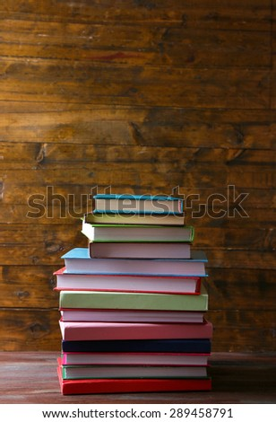 Stack of books on table on wooden background
