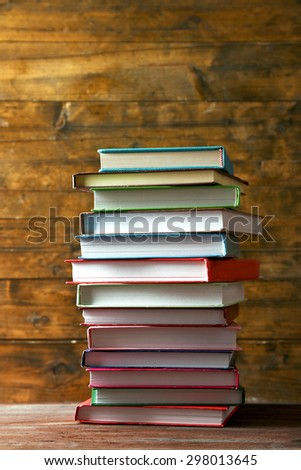 Stack of books on table on wooden background - stock photo