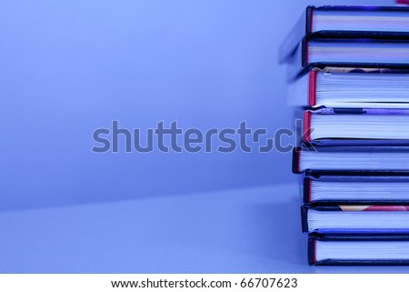 stack of books on the table in blue color. with copy-space - stock photo