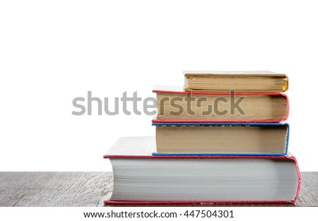 Stack of books on the table with isolated background - stock photo