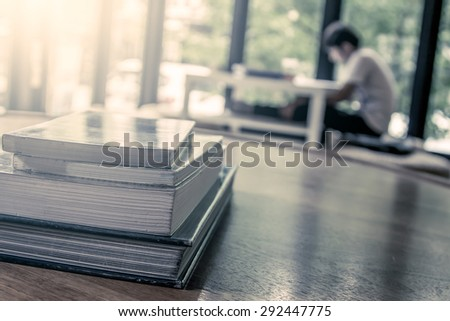 stack of books on wooden table on blur people read a book background in vintage color filter - stock photo