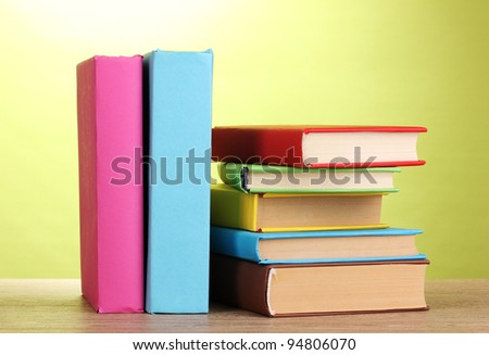 Stack of books on wooden table on green background - stock photo