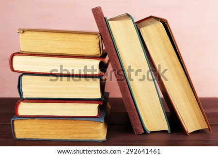 Stack of books on wooden table on pink wall background - stock photo