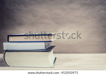Stack of books on wooden table. Vintage style photo