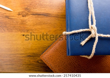 Stack of books tied with a rope on wooden background. Back to school. Copy space for your text. - stock photo