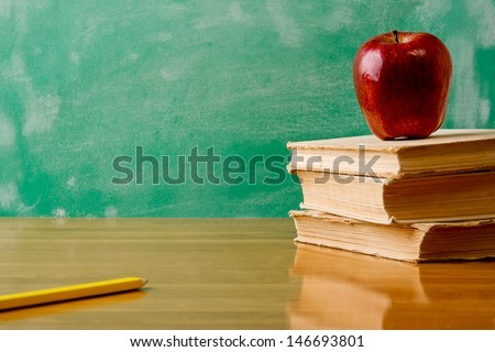 Stack of books with apple and  pencil . Isolated on green
