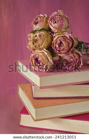 stack of books with bunch of roses, close up, free copy space - stock photo