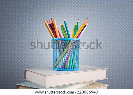 Stack of books with color wooden pencils in blue holder basket.