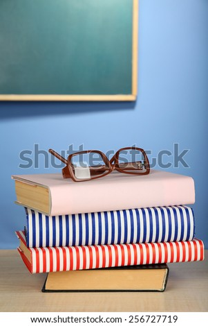 Stack of books with glasses on wooden desk, on colorful wall and blackboard background - stock photo
