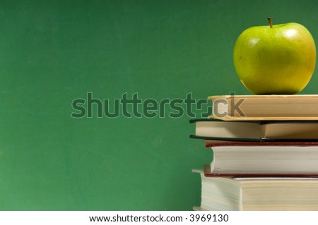 Stack of books with granny smith apple on a green background