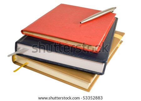 Stack of books with notepad and pen