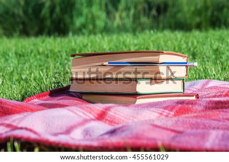 stack of books with pencil on pink plaid in the student park - stock photo