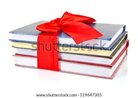 Stack of books with ribbon isolated on white - stock photo