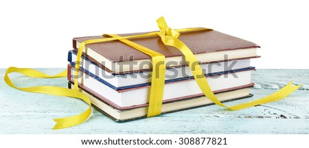 Stack of books with ribbon on table isolated on white - stock photo