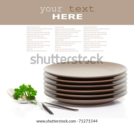 Stack of brown round plates with fork, spoon and parsley (with sample text) - stock photo