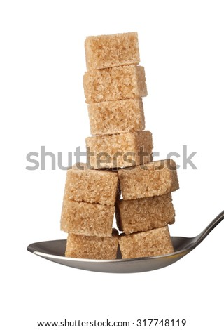 Stack of brown sugar cubes on a spoon isolated on white background