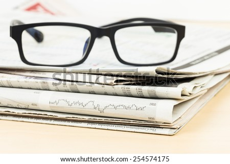 Stack of business newspapers on table with glasses - stock photo