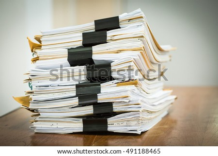 Stack of business report paper files with black clips
