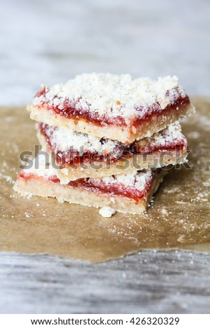 Stack of cake or cookies with plum, strawberry, raspberry and cherry jam or marmalade with sweet crumbs, cinnamon and nuts on a parchment paper - stock photo