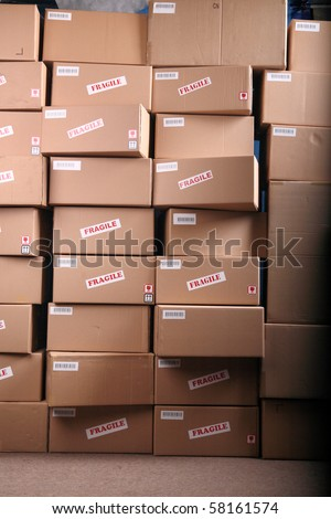 Stack of cardboard boxes in a warehouse - stock photo