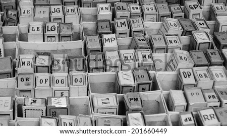 Stack of cardboard boxes with alphabet letters  and syllables. Vintage game at flea market. Aged photo. Black and white.
