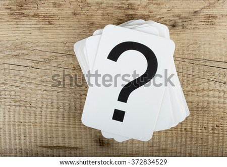 Stack of cards with a question mark on the old wooden background
