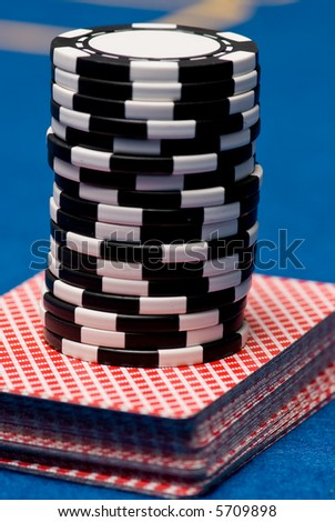 Stack of cards with chips ontop - stock photo