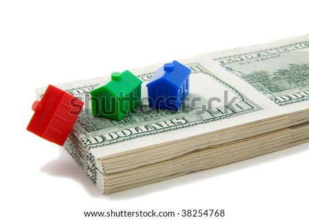 Stack of cash with models of houses in a row, red house on the edge, falling down - stock photo