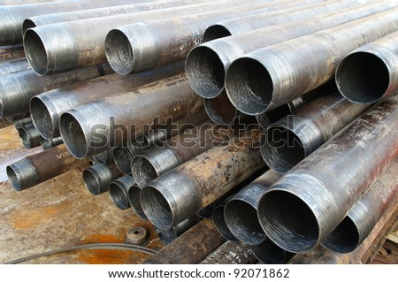 Stack of casing laying on the deck before running in the oil well - stock photo