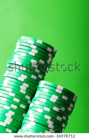 Stack of casino chips against green background - stock photo