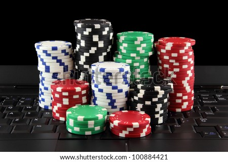 stack of casino gambling chips on keyboard, on-line gaming concept - stock photo