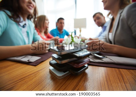 Stack of cellphones with group of friends on background - stock photo