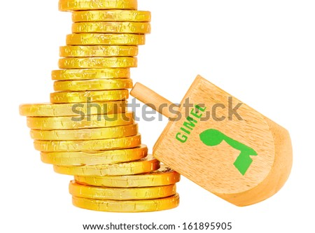 Stack of Chanukah gelt, coins, large wood dreidel.Traditional game for the Jewish holiday of Chanukah.Hebrew letter gimel wins the group of shiny wrapped yellow coins.Isolated on a white background. - stock photo