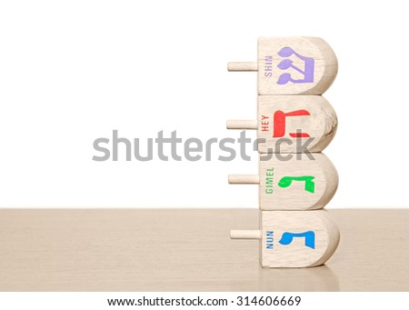 Stack of 4 Chanukah wooden dreidels on a wood surface. Side view with the Hebrew letters nun, gimel, hey, shin. Shallow depth of field, drop shadow. Copyspace. Isolated on a white background.  - stock photo