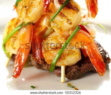 Stack of chargrilled shrimps tied up with chives on top of a grilled steak. - stock photo