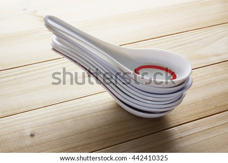 Stack of Chinese Soup Spoons on Wooden Background - stock photo