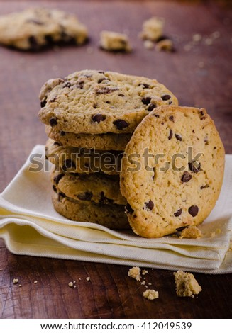 Stack of chocolate chip cookies on wooden table close up