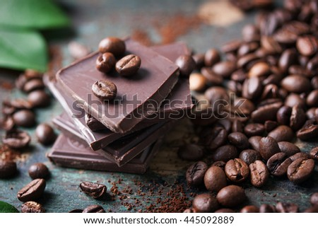 Stack of chocolate chunks with coffee beans on a wooden background, closeup