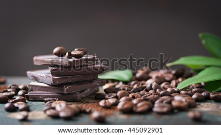 Stack of chocolate chunks with coffee beans on a wooden background, horizontal with copy space - stock photo
