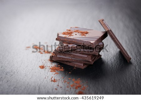 Stack of chocolate chunks with mint on a dark stone background with cocoa, closeup, with copy space - stock photo