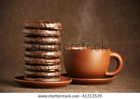 Stack of chocolate cookies and cup of coffee on brown canvas. - stock photo