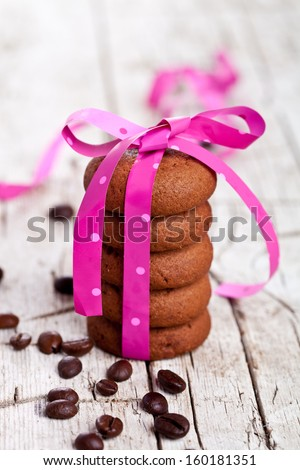 stack of chocolate cookies tied with pink ribbon and coffee beans on rustic wooden background - stock photo