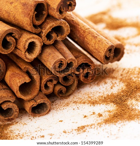 Stack of cinnamon with its dust around it over a white background - stock photo