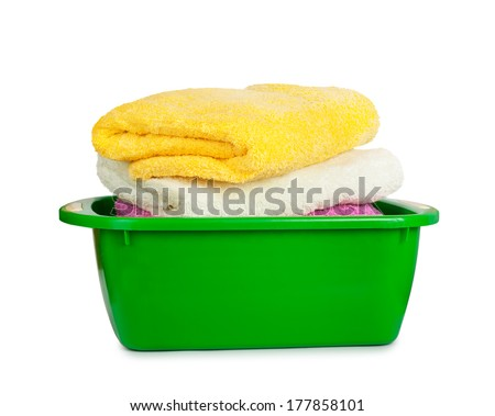 Stack of clean fresh towels in the green basin isolated on white background