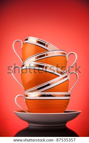 Stack of coffee cups on red background - stock photo