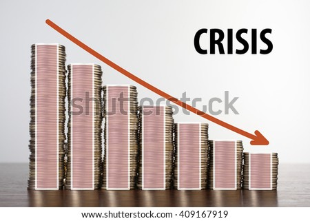 Stack of coins and graph down - stock photo