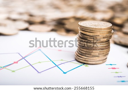 Stack of coins and graph on background - stock photo