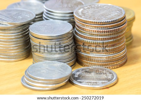 stack of coins isolated on wood table background - stock photo